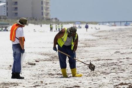 Hai công nhân dọn dẹp một khu vực có dầu