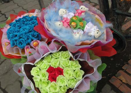 Ngọt ngào hơn với sự kết hợp của hoa giấy, gấu bông cùng những thanh kẹo. Đây như một lời chúc dành cho tình yêu đôi lứa vừa lãng mạn như hoa, vừa ngọt ngào như kẹo, chỉ tay vào bó hoa màu xanh, cô bạn kinh doanh mặt hàng này lý giải.