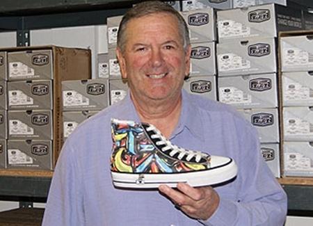 Ông John với sản phẩm giày có khóa kéo của mình.