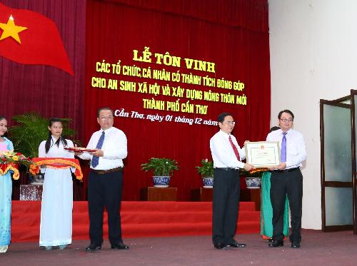 Được sự ủy quyền của Ban Lãnh đạo Vietcombank, ông Trần Long Giang - Phó giám đốc phụ trách điều hành Chi nhánh Vietcombank Cần Thơ (ngoài cùng bên phải) nhận bằng khen vinh danh của Thành ủy Thành phố Cần Thơ