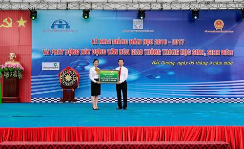 Bà Nguyễn Thị Thêu - Giám đốc Vietcombank Hải Dương (bên trái) trao biển tượng trưng 1.500 mũ bảo hiểm cho đại diện nhà trường