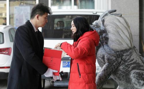 Khách hàng kiểm tra món hàng hiệu mà cô mua quamạng, được giao bằng dịch vụ VIP. Ảnh: Reuters.