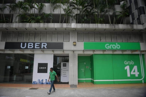Uber đầu tuần này đã tuyên bố bán mảng Đông Nam Á cho Grab. Ảnh: Straits Times