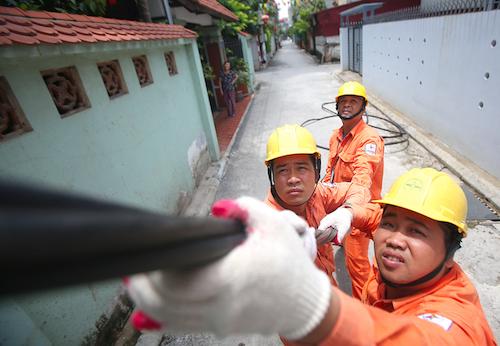 Công nhân Công ty Điện lực Long Biên kéo dây tăng truyền tải trên địa bàn. Ảnh: Ngọc Thành