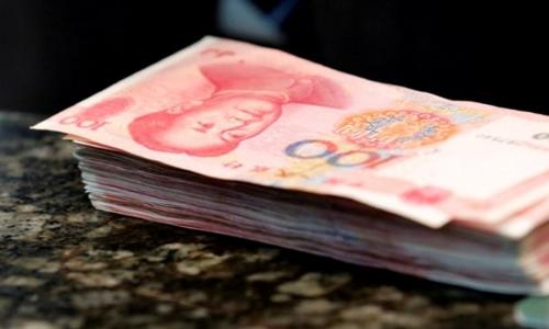 Các tờ 100 NDT trên quầy giao dịch ở 1 ngân hàng ở Bắc Kinh. Ảnh: Reuters