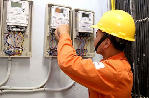 Kiểm tra công tơ của công nhân ngành điện. Ảnh: PV