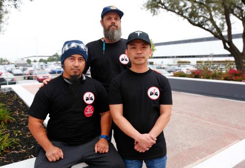 Mikey Catura ngồi bên trái và Hai Nguyen đứng cạnh bên phải chụp trước nhà máy Tesla ở Fremont, California vào tháng 8/2017. Ảnh: The Mercury News