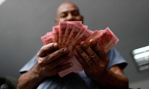 Một nhân viên đang đếm tiền ở 1 bãi giữ xe ở Caracas (Venezuela). Ảnh: Reuters