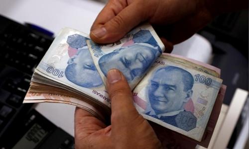 Nhân viên đang đếm lira ở 1 quầy đổi tiền ở Istabul. Ảnh: Reuters