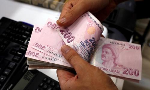 Nhân viên kiểm tiền ở 1 quầy đổi ngoại tệ ở Istanbul. Ảnh: Reuters