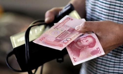 Người mua hàng cầm tờ 100 NDT tại một khu chợ ở Bắc Kinh. Ảnh: Reuters