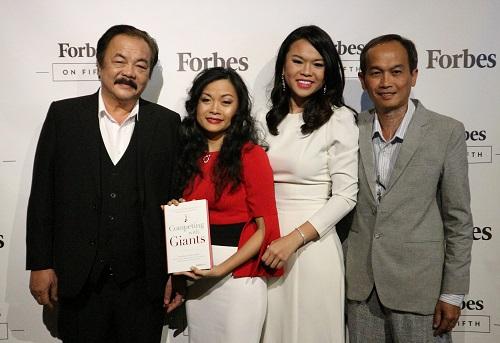 Ông Trần Quí Thanh và hai con gái Trần Uyên Phương và Trần Ngọc Bích (từ trái sang) chụp hình lưu niệm cùng khách mời ở sự kiện. Ảnh: K.A.