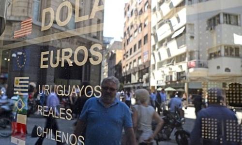 Bên ngoài 1 bảng tỷ giá trên đường phố Argentina. Ảnh: AFP