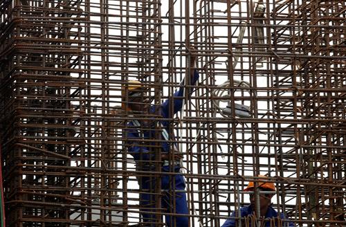 Công nhân thực hiện hàn cột ở 1 công trường thi công. Ảnh: Reuters