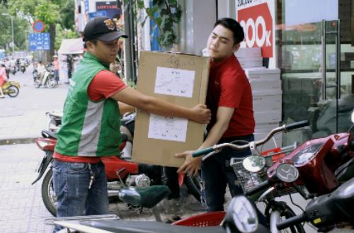 Nhân viên một đơn vị chuyển phát nhanh đàng giao hàng cho khách.