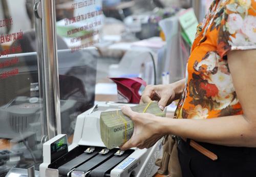 Giao dịch tiền mặt tại ngân hàng thương mại ở Hà Nội. Ảnh:Anh Quân.