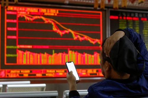 Nhà đầu tư tại một công ty môi giới chứng khoán ở Bắc Kinh (Trung Quốc). Ảnh: Reuters