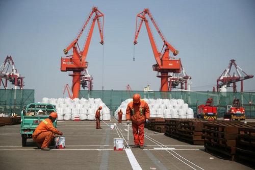 Công nhân đang sơn lại nền tại một cảng của Thanh Đảo, Sơn Đông, Trung Quốc. Ảnh: Reuters