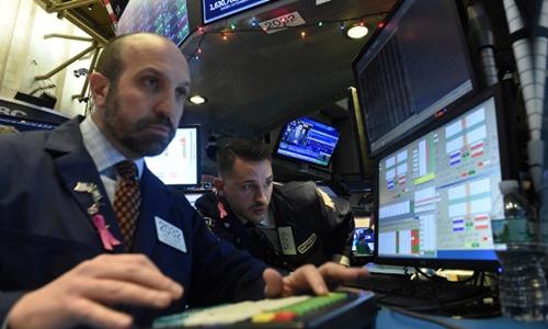 Nhân viên giao dịch làm việc trên sàn NYSE (Mỹ) hôm qua. Ảnh: Reuters