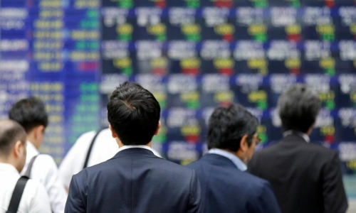 Người dân đi qua một bảng điện tử hiển thị giá cổ phiếuở Nhật Bản. Ảnh: Reuters
