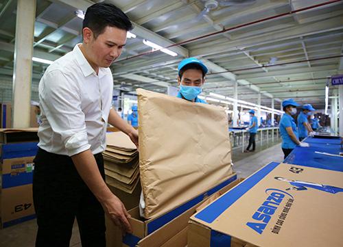 Ông Phạm Văn Tam - Chủ tịch Asanzo (áo trắng) quyết định sử dụng bao bì giấy để góp phần bảo vệ môi trường.