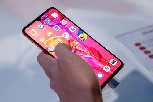 Một khách hàng sử dụng điện thoại của Huawei tại sự kiện ra mắt ở Paris. Ảnh: Bloomberg