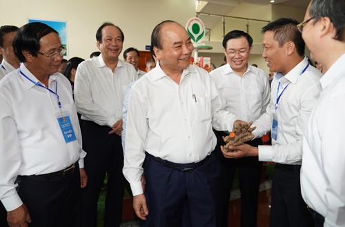 Thủ tướng tham quan các gian hàng của doanh nghiệp tại Hội nghị ngày 25/6. Ảnh: VGP.