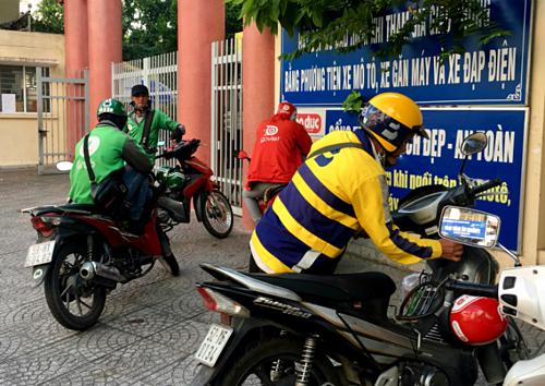 Tài xế Grab, be, Go-Viet đỗ xe ở một cổng trường tại quận Bình Thạnh, TP HCM. Ảnh: Viễn Thông