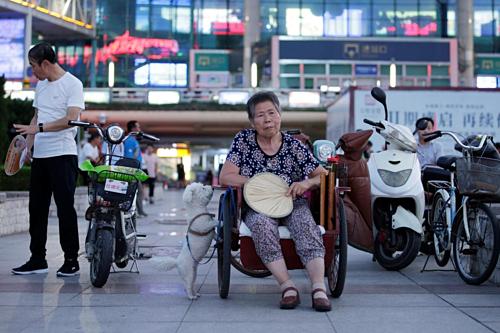 Một phụ nữ 68 tuổi đang ngồi hóng mát ở quảng trường tại Duy Phường, Sơn Đông. Ảnh: Reuters