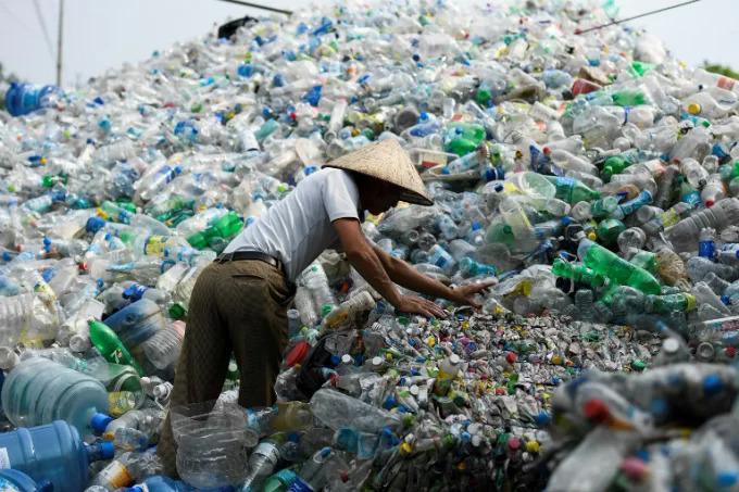 Người đàn ông nhặt chai nhựa đã qua sử dụng tại một bãi rác ở Hà Nội, tháng 6/2018.Ảnh: AFP/Nhac Nguyen.