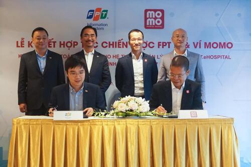 Ông Nguyễn Hoàng Minh, Tổng giám đốc Công ty Hệ thống Thông tin FPT (ngồi bên trái) và ông Phạm Thành Đức, Tổng giám đốc Ví MoMo (ngồi bên phải) ký kết hợp tác chiến lược.