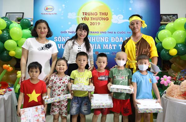 Bà Nguyễn Thị Vũ Thành (áo trắng, ở giữa), Phó tổng giám đốc Công ty Cổ phần Dược phẩm GoldHealth Việt Nam tặng quà Trung thu cho các em nhỏ.
