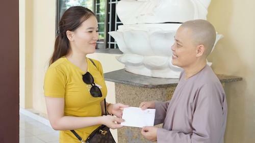 Đại diện Viện thẩm mỹ Diva trao tiền hỗ trợ để chùa có thêm kinh phí nuôi dưỡng các em nhỏ.