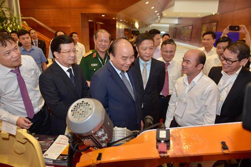 Thủ tướng Nguyễn Xuân Phúc thăm gian hàng của một doanh nghiệp cơ khí, bên lề hội nghị ngày 24/9. Ảnh: VGP