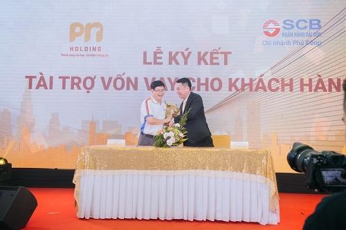 Ông Nguyễn Phúc Nam tặng hoa cảm ơn đại diện SCB sau nghi thức ký kết hợp tác.