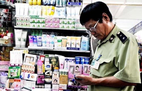 Cán bộ quản lý thị trường Hà Nội kiểm tra một quầy bán mỹ phẩm tại chợ Đồng Xuân. Ảnh: HNM