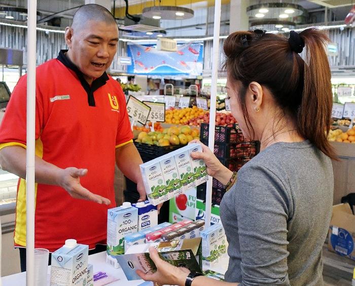 Người tiêu dùng tìm hiểu về sữa tươi organic tại các quầy dùng thử sản phẩm sữa Vinamilk trong siêu thị ở Singapore.