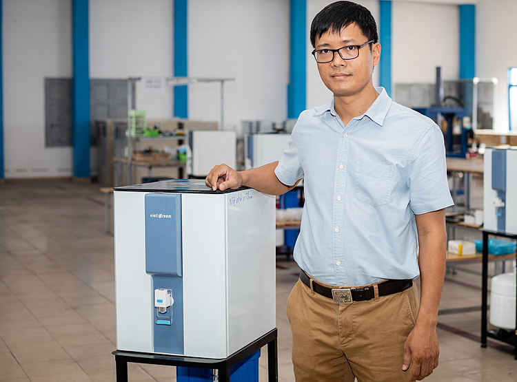 Đỗ Hữu Quyết bên chiếc máy lọc nước do mình tự sáng chế. Ảnh: Thành Nguyễn.
