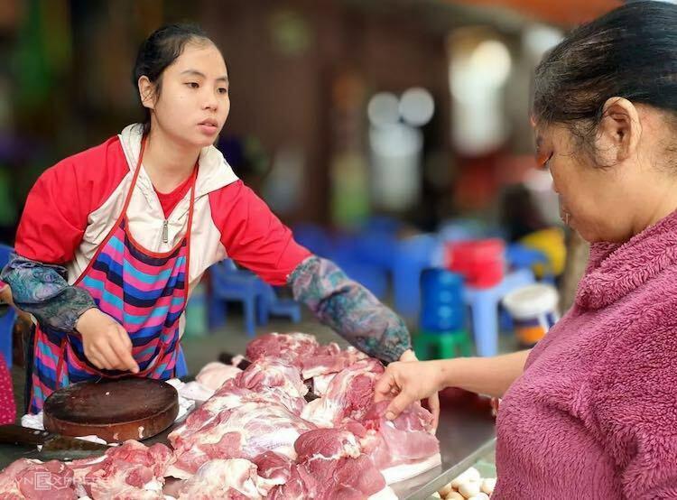 Người dân chọn mua thịt heo tại một chợ ở Hà Nội. Ảnh: Anh Minh
