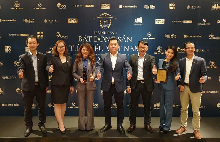 Ông Phạm Lâm - CEO DKRA Vietnam (đứng giữa) cùng các cấp quản lý và lãnh đạo các công ty thành viên nhận giải thưởng do Nhịp Cầu Đầu Tư và hội đồng thẩm định trao tặng