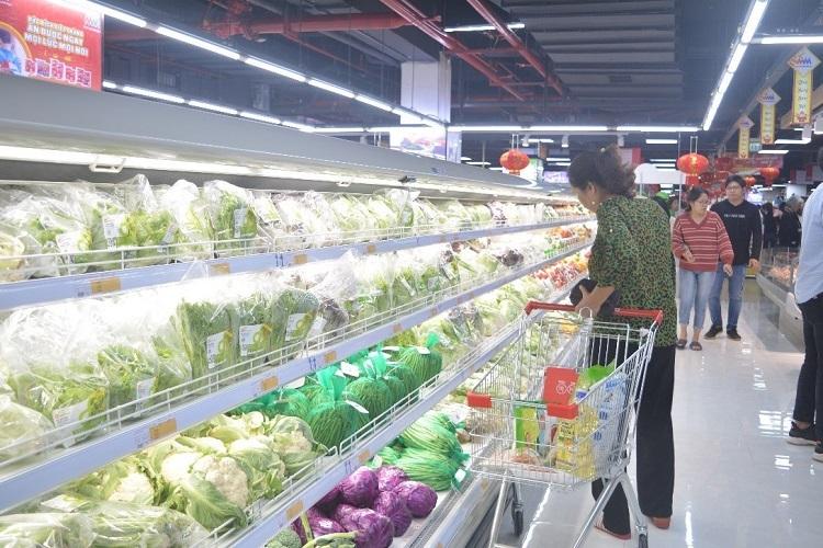 Một khách hàng mua sắm tại quầy rau trong siêu thị.