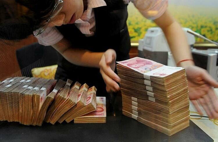 Nhân viên một ngân hàng ở An Huy (Trung Quốc) đang kiểm tiền. Ảnh: Reuters