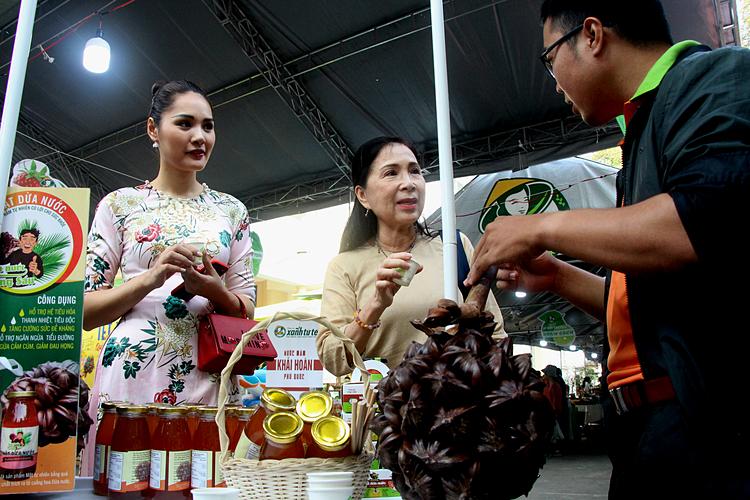 Từ trái sang, Hoa hậu Hương Giang, NSND KIm Xuân tại quầy bán mật dừa nước. Ảnh: Trần Quỳnh