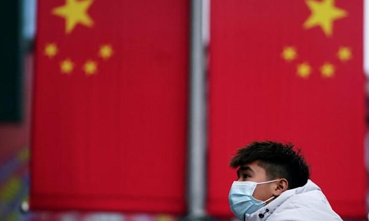 Một người đeo khẩu trang đi bộ trên đường phố Thượng Hải hôm 24/1. Ảnh: Reuters