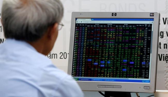 Nhà đầu tư theo dõi bảng giá điện tử. Ảnh: Reuters.