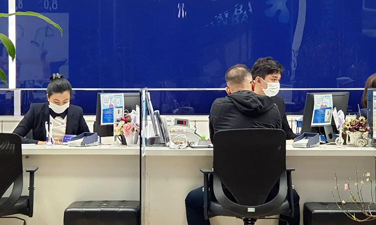 Giao dịch viên một ngân hàng được yêu cầu đeo khẩu trang khi làm việc để phòng chồng virus nCoV. Ảnh: Anh Tú.