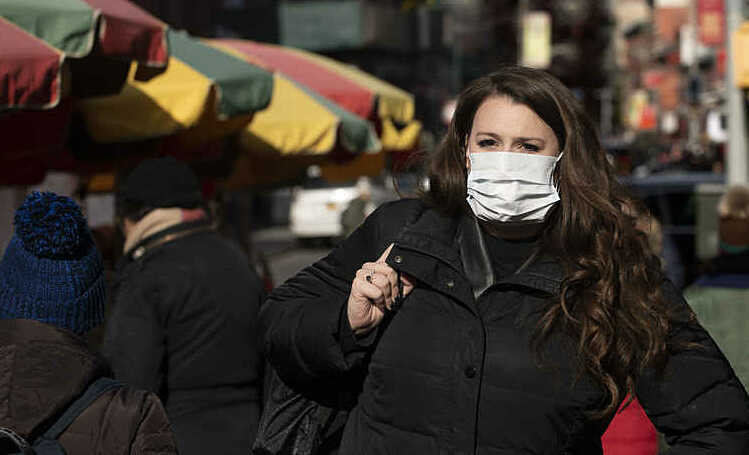 Một người Mỹ đeo khẩu trang trên đường phố New York. Ảnh: AP