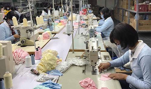 Công nhân một nhà máy sản xuất khẩu trang đang làm việc. Ảnh: AM