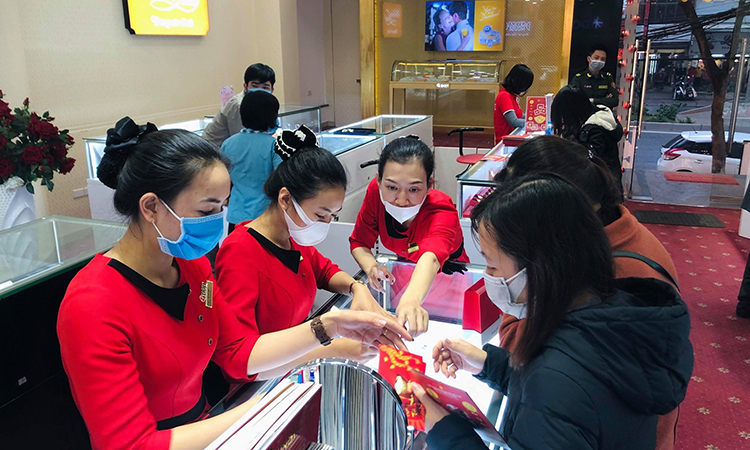 Gần 11h trưa, ba nhân viên cùng tư vấn cho khách chọn mua vàng tại một cửa hiệu trên phố Cầu Giấy, Hà Nội. Ảnh: AT