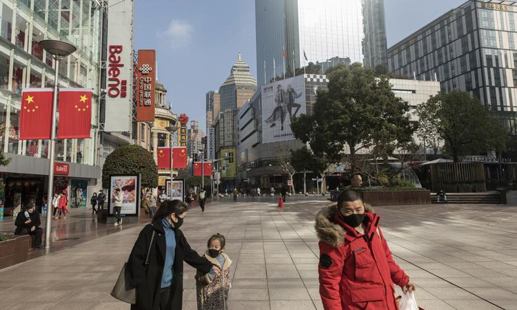 Người dân đi ngang qua các cửa hàng ở Thượng Hải. Ảnh: Blooomberg.